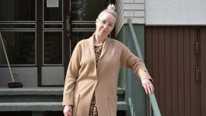 Kvinna i beige kappa framför höghus.