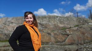Ung kvinna med brunt hår och orange halsduk står vid stenig klippa