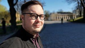 Ung man med svarta glasögon tittar ut över ett tomt torg