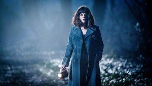 Nainen kävelee ulkona iltahämärässä taskulampun kanssa.