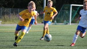 Två spelare springer efter bollen på fotbollsplanen.