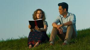 Nuori amerikkalainen nainen ja korealainen mies istuvat nurmikolla, naisella on kirja kädessään.