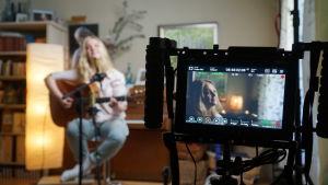 Musikern Tove Ljungqvist spelar gitarr och sjunger framför en videokamera i sitt hem.