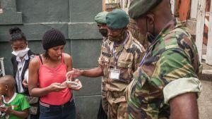 """Soldater delar ut ansiktsmasker och """"örtmedicinen"""" (här som örtte) i centrum av Antananarivo."""