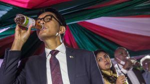 """Madagaskars president Andry Rajoelina drack ur en flaska """"Covid Organics"""" vid lanseringsceremonin för """"örtmedicinen"""" i huvudstaden Antananarivo den 20 april."""