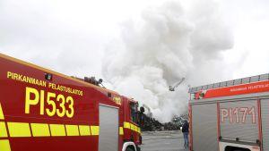 Ett enormt rökmoln bakom ett par brandbilar.