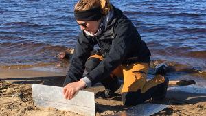 WWF:n meriasiantuntija Anna Soirinsuo kerää näytteitä Nallikarin hiekkarannalla mikromuovin määrän selvittämiseksi.