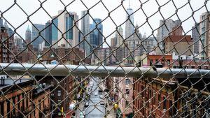 Hiljainen suurkaupungin katu kuvattuna verkkoaidan läpi. Yksi ihminen näkyy keskellä katua. Taustalla näkyy pilvenpiirtäjiä.