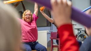 Fysioterapeut ger instruktioner till äldre under stolgymnastiken.