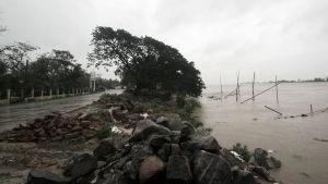 Vattennivån är hotande vid en kustväg i Odisha i Indien då stormen Amphan drar in över land.