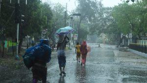 Personer går mot ett stormskydd. Det regnar massor och de håller upp paraplyn och bär på tunga packningar.
