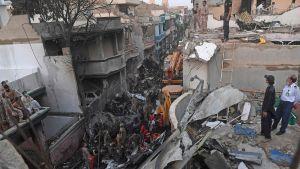 Pelastustyöntekijät etsivät eloonjääneitä matkustajalentokoneen raunioista Pakistanin Karachissa.