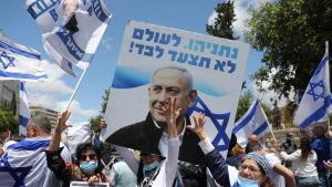 """Netanyahhus anhängare samlades utanför domstolsbyggnaden under banderoller med texten """"Benjamin Netanyahu går aldrig ensam."""""""