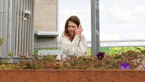 Kuvassa ympäristöbiologi Taina Suonio, etualalla kukkapenkki, jossa orvokkeja.
