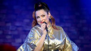 Erin laulaa kultainen mekko yllään.