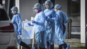 Vårdpersonal i Vanda iklädd skyddsutrustning för att undvika coronasmitta. De jobbar med drive-in-testning.