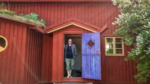 Mies seisoo talonsa ovella.