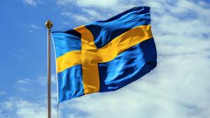 En fladdrande svensk flagga mot blå himmel