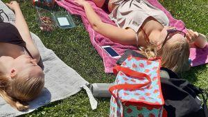 Två tonårstjejer Wilma och Elin solbadar på varsin filt med kylväska och mobilerna med sig på en gräsmatta