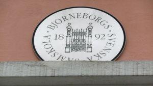 En rund skylt, med texten Björneborgs svenska samskola 1892, är uppsatt på en tegelvägg.