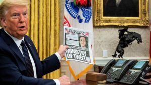 Turmp istuu pöydän takana ja esittelee lehteä, jossa pääosikko on: Ministry of Tweet eli Twitter-ministeriö.