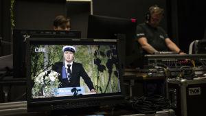 Tuukka Rajala näkyy monitorilla puhumassa. Taustalla lähetyksen ohjaamo.