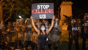 Kvinna håller upp skylt där det står ''Sluta döda oss'', i bakgrunden står kravallpolis i full mundering.