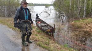 Ivalolainen Ilkka Ollila veneensä kanssa tulvivan Ivalojoen rannalla.
