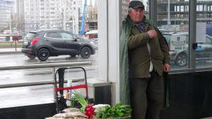 En man säljer grönsaker på gatan i Vitryssland.