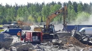 Män och arbetsmaskiner bland stenar som sprängts på Ingåport.