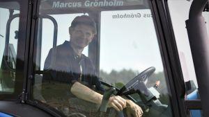 Marcus Grönholm i traktor på åkern utanför hemmet i Ingarskila.