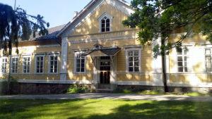 En gul äldre träbyggnad där det står Seminarium på fasaden.