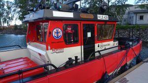 Röd räddningsbåt med stor förarhytt står parkerad vid brygga.
