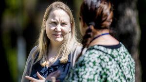 Jutta Peltoniemi, en kvinna med blont hår, samtalar med Tiia Leino, en kvinna med brunt hår och mönstrad blus.
