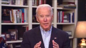 Joe Biden klädd i kostym tittar in i kameran och pratar. I bakgrunden syns en bokhylla.