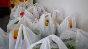 Valkoisia muovipusseja täynnä ruokaa.