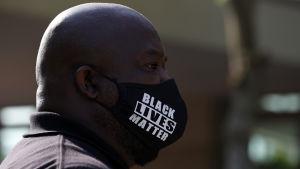 En man bär en skyddsmask med texten Black lives matter.