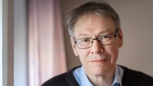 Krister Petersson - åklagare och chef för Palmeutredningen. Han ser rakt in i kameran och har glasögon med svarta bågar.