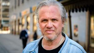 Henrik Frölich iklädd svart skjorta och jeansjacka. Han har gråaktigt hår och skägg.