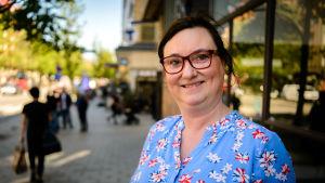 Therese Elias-Gomes är klädd i en blåblommig sommarklänning. Hon har glasögon och ser glad ut.