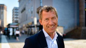 Olle Jonsson är klädd i svart kavaj och blårutig skjorta. Han ser glad ut.