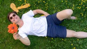 Puutarhuri Anna Palasmaa makaa kukkien keskellä puutarhassaan ja ihastelee kasvattamaan unikkoa