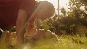 En man och en kvinna ligger på en äng.