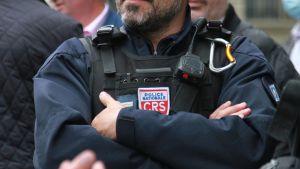 En polis står med armarna i kors.