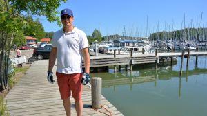 Jukka Rajala, en man klädd i blå keps, solglasögon, vit t-skjorta och röda shorts, står ute på en brygga.