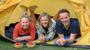 BUU-klubbsledarna Malin, Lisa och Jontti ligger på mage i ett tält och tittar mot oss genom i tältöppningen