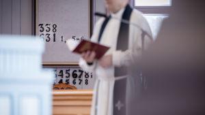 En präst håller i en psalmbok i kyrkan.