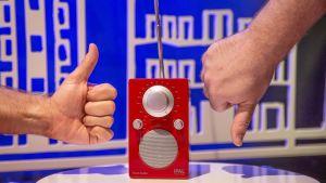Peukku ylös ja peukku alas radion vieressä.