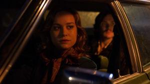 Brie Larsonin hahmo istuu auton ratissa ja katsoo ulos. Takapenkillä istuu mies.