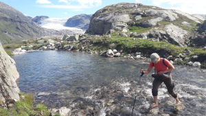 En vandrare tar sig barfota över en fjällbäck.
